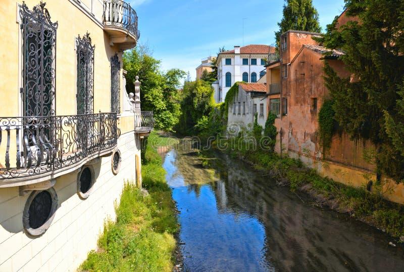 Costruzioni variopinte, architettura, riflessioni dell'acqua sul canale della città e vecchia facciata con cielo blu a Padova Ven immagine stock libera da diritti