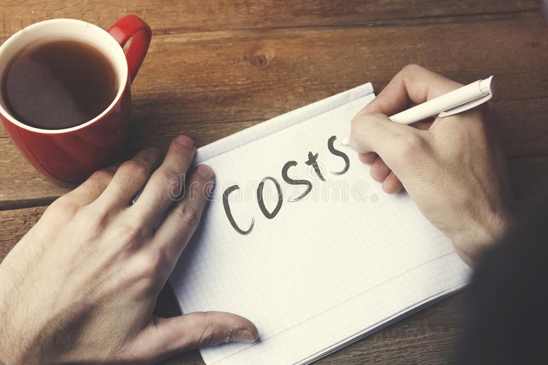 Costs text on notepad. And man hand pen on working table stock photos