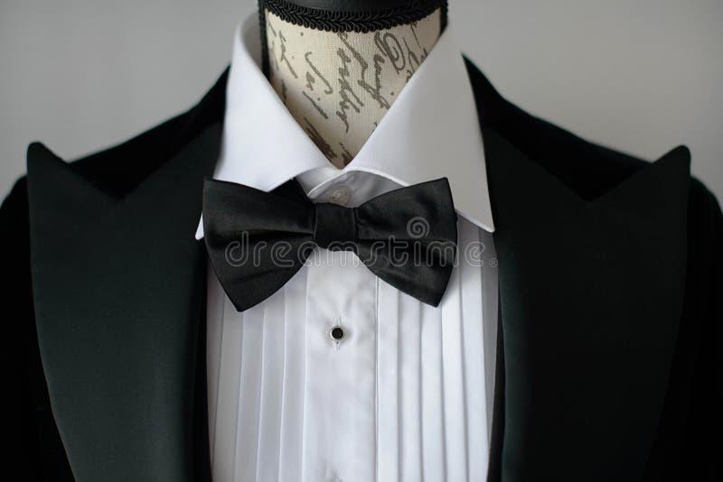 Costume élégant de lien noir avec le noeud papillon de chemise et en soie blanc sur le torse de mannequin ou une forme de robe image libre de droits