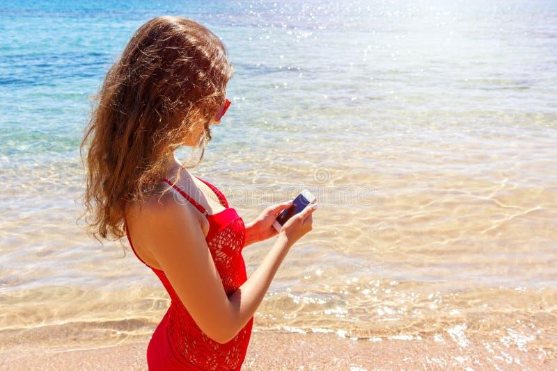 Costume da bagno d'uso della ragazza del Sunbather facendo uso di uno Smart Phone Vacanze estive sulla spiaggia fotografia stock libera da diritti