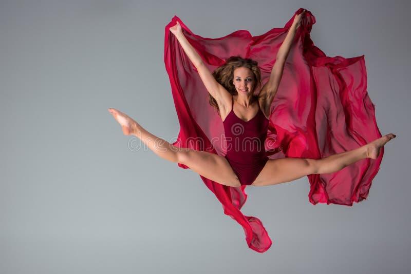 Costume da bagno marrone rossiccio d'uso del bello ballerino della donna che posa su un fondo grigio dello studio immagini stock libere da diritti