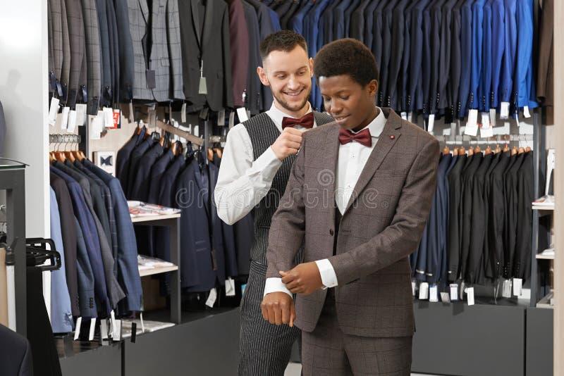 Costume de choix auxiliaire dans la boutique à la mode pour le client photos stock