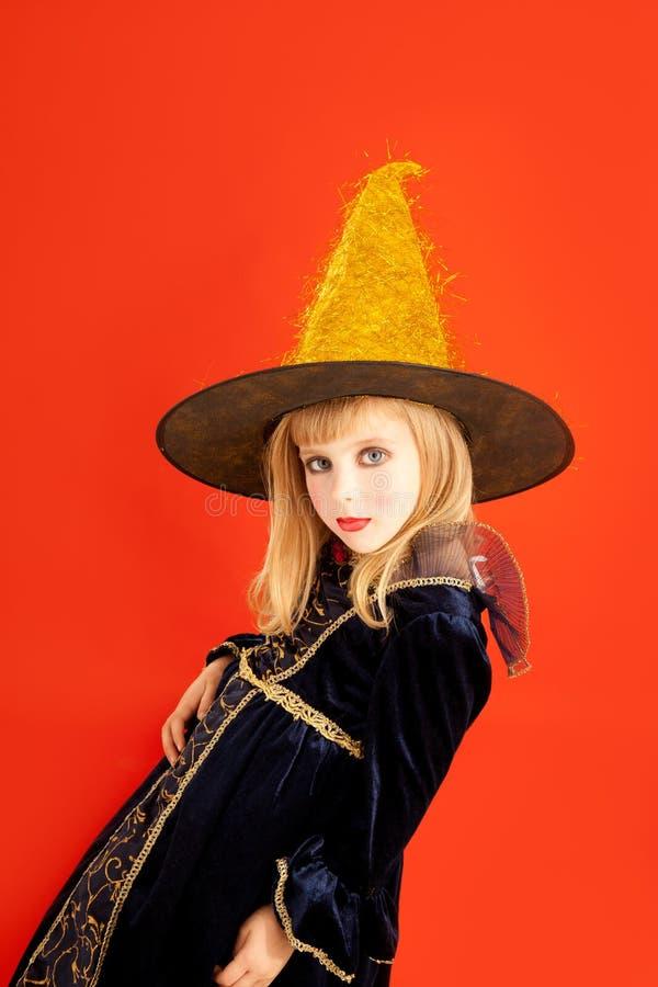 Costume de fille de gosse de Veille de la toussaint sur l'orange photo stock