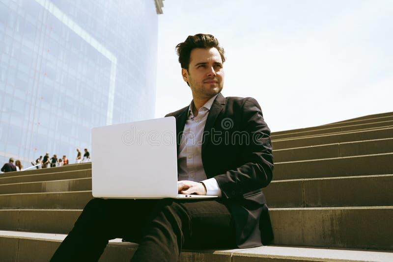 Costume de port d'homme d'affaires attirant et à l'aide de l'ordinateur portable moderne dehors Banquier réussi travaillant dehor images libres de droits
