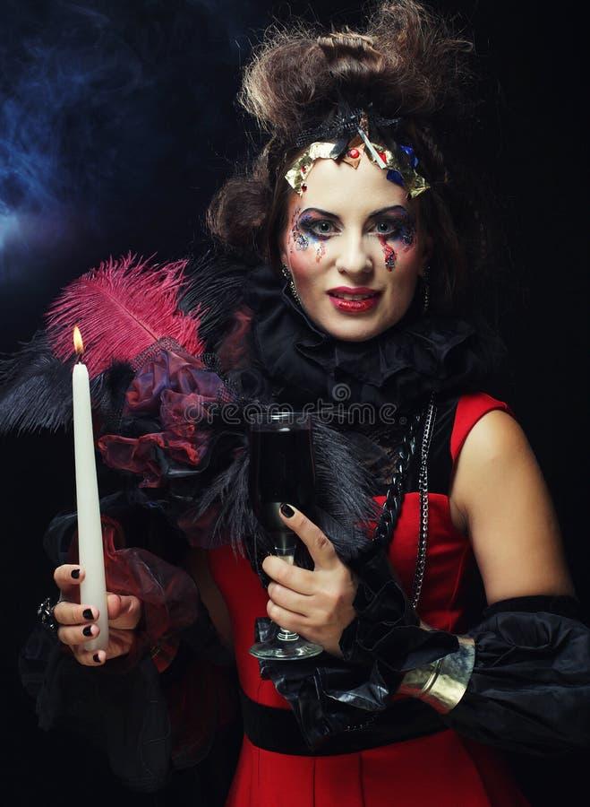 Costume de port de carnaval de jeune femme tenant une bougie images libres de droits