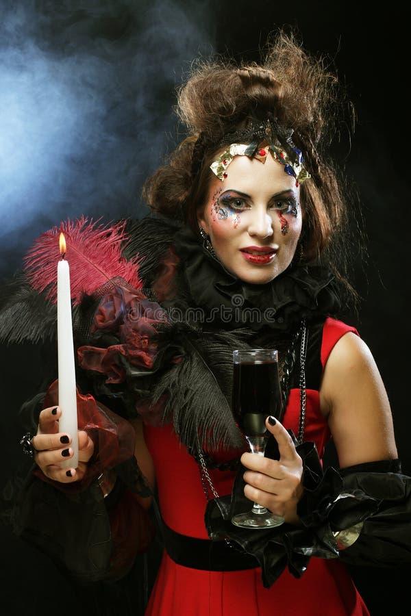 Costume de port de carnaval de jeune femme tenant une bougie photographie stock libre de droits