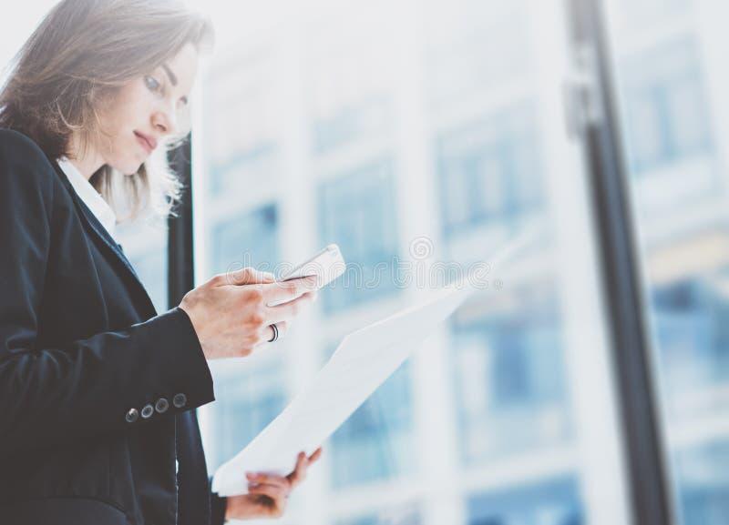 Costume de port de femme d'affaires de photo, regardant le smartphone et tenant des documents dans des mains Bureau de grenier de images stock