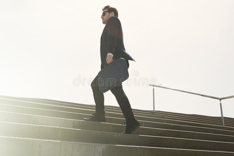 Costume de port et fonctionnement de jeune homme d'affaires confidentiel rapidement en haut Tir horizontal d'extérieur photographie stock