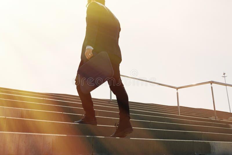 Costume de port et fonctionnement de jeune homme d'affaires confidentiel rapidement en haut Tir horizontal d'extérieur Effet enso photos stock
