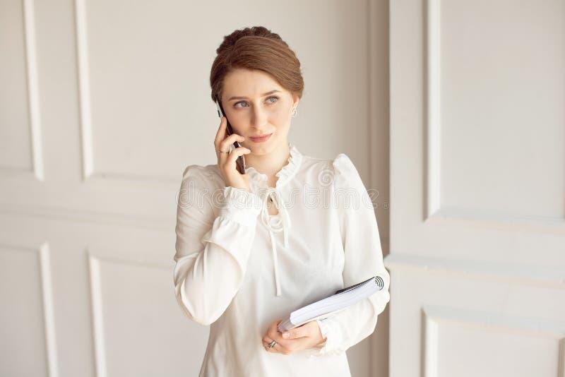 Costume de port de femme d'affaires de photo, regardant le smartphone et tenant des documents dans des mains photo stock