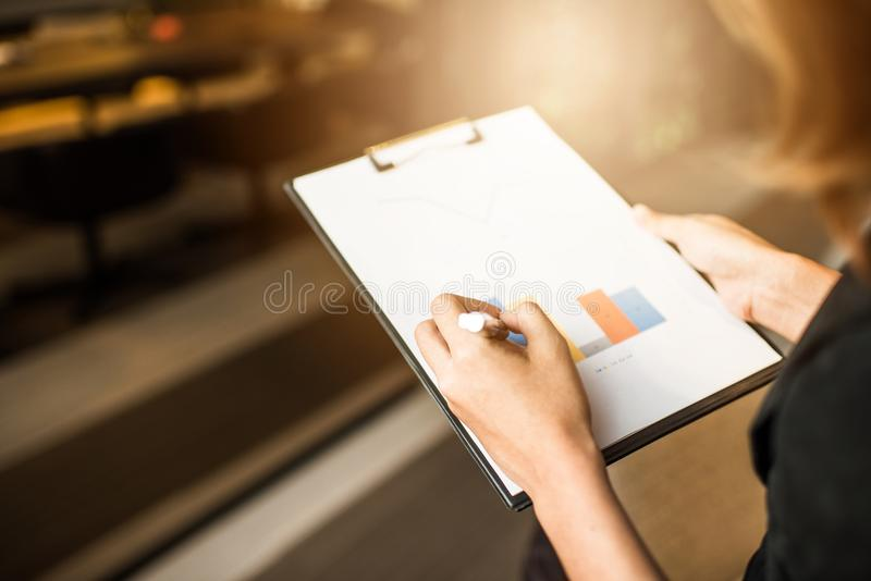 Costume de port de femme d'affaires, regardant des documents dans des mains photographie stock libre de droits