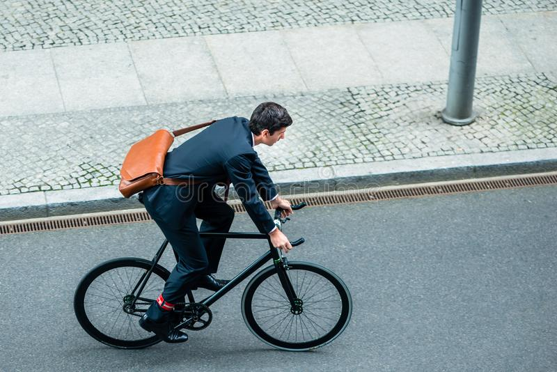 Costume de port de jeune homme tout en montant une bicyclette de service photos libres de droits