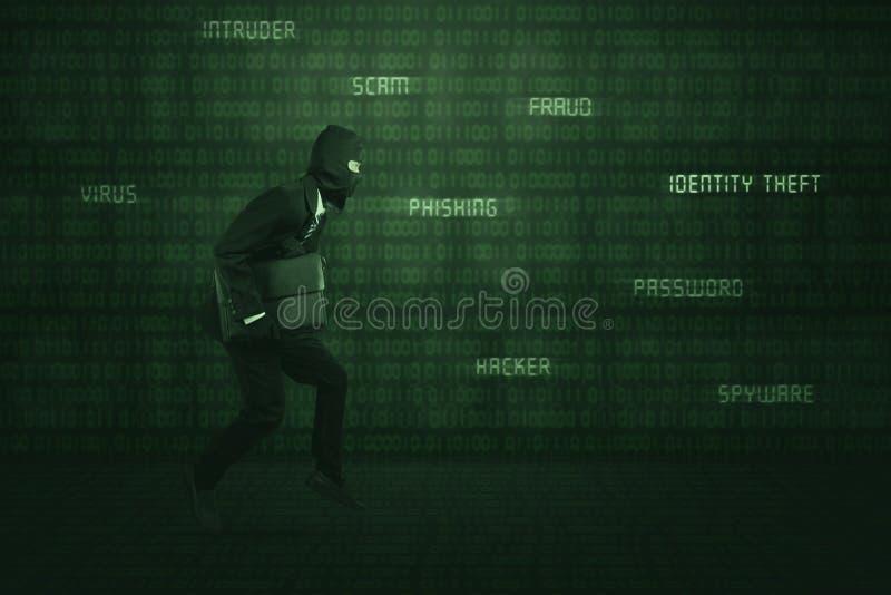 Costume et masque de port de voleur fonctionnant volant l'ordinateur portable image stock