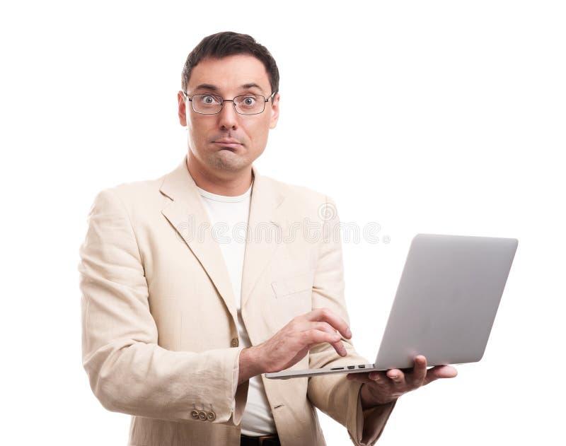 Costume et verres de port étonnés d'homme avec l'ordinateur portable image stock