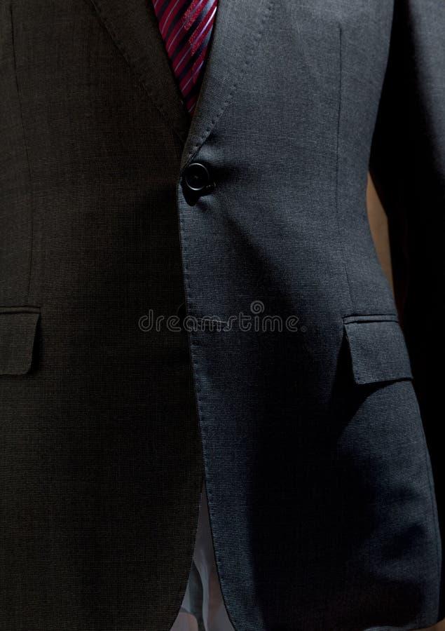 Costume gris avec le bouton de costume photographie stock
