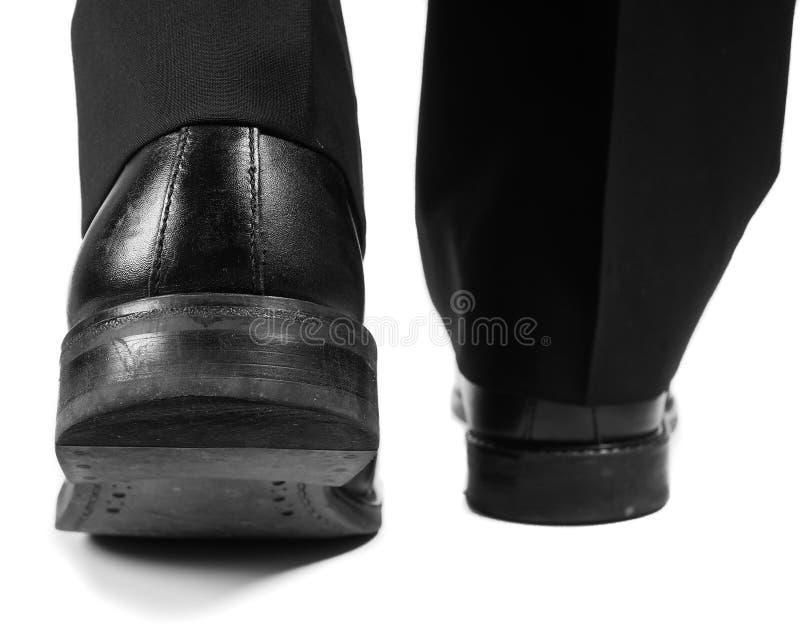 Costume masculin marchant loin dans des chaussures noires image stock