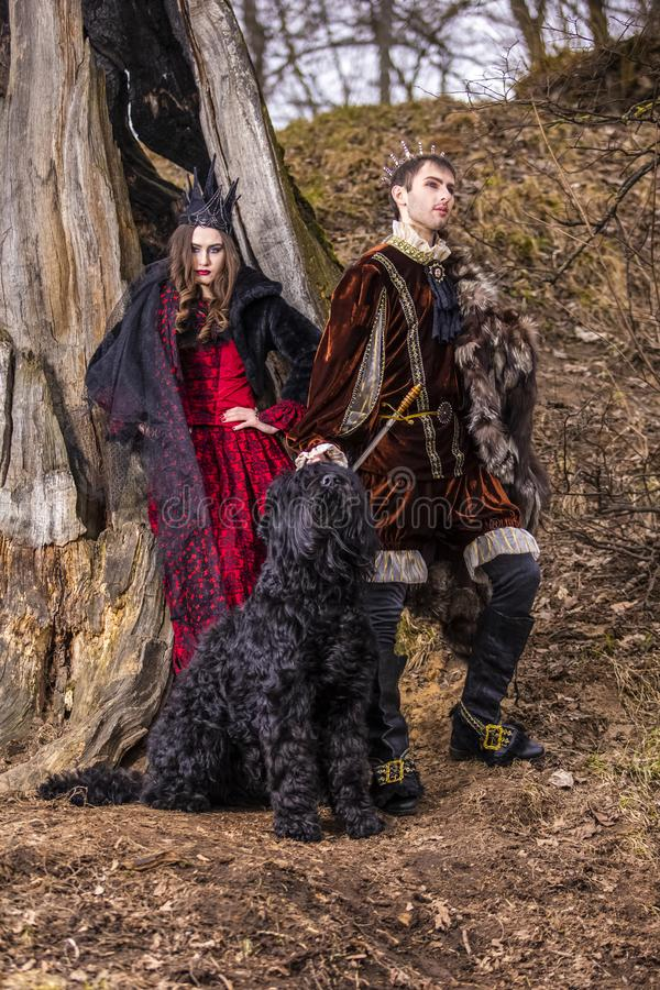 Costume Play Project. Caucasian Couple as Prince and Princess with Black Dog Posing in Medieval Clothing in Spring Forest Outdoors stock image