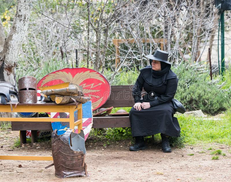 A Costumed Doctor Death sits near a warehouse with armor and shields at the Purim Festival with King Arthur in the city of Jerusal stock photos
