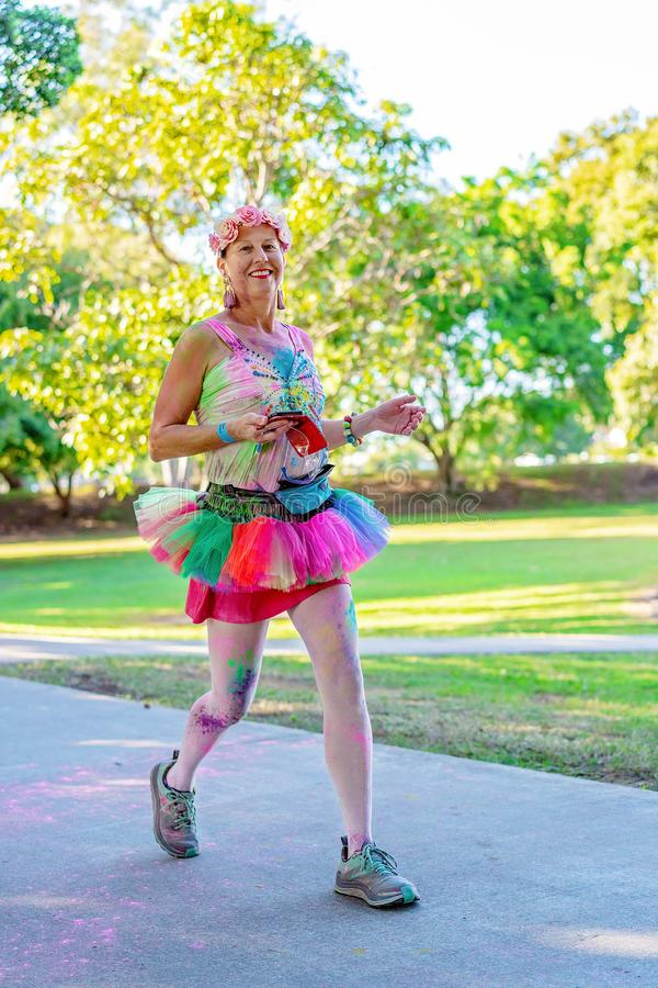 Costumed Woman Walking Happily In Color Fun Run stock photo