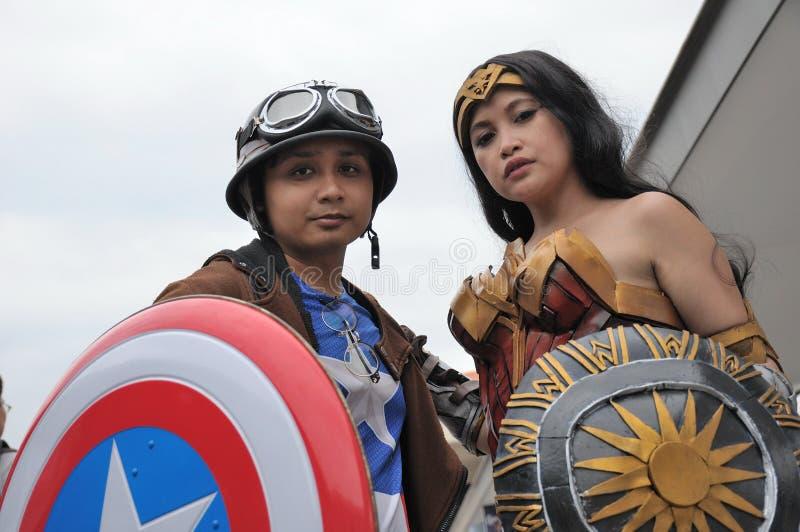 Costumers jouant un rôle la femme de capitaine America et de merveille photos stock