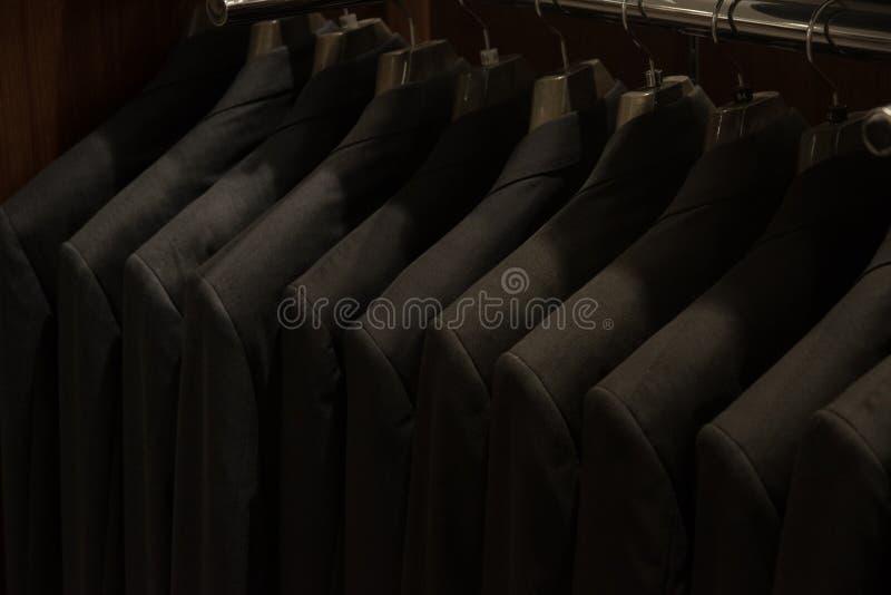 Costumes pour les hommes au magasin de mode des hommes photo stock