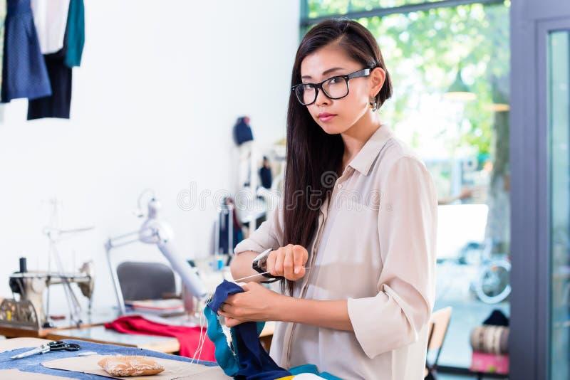Costura asiática da mulher do desenhador de moda em sua oficina fotos de stock