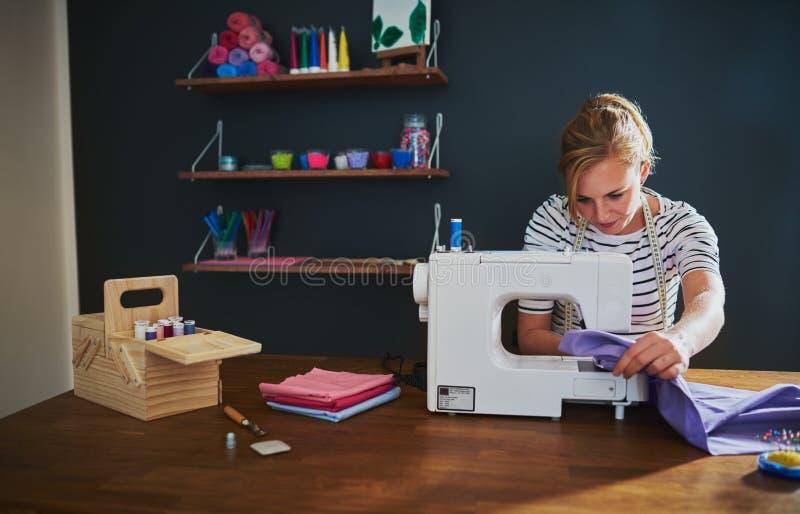 Costura da mulher em uma máquina de costura foto de stock royalty free