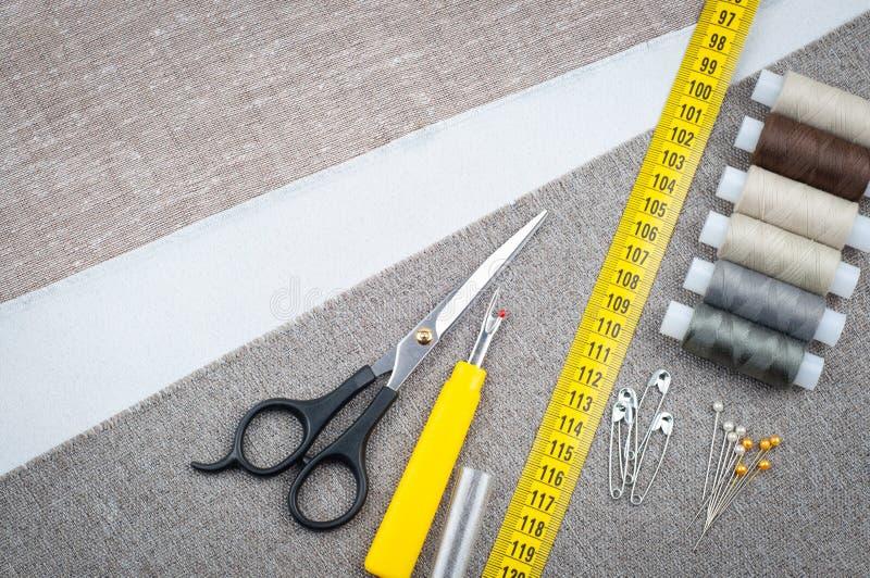 Costurando a composição do teste padrão com tesouras, carretéis da linha, pinos, fita de medição imagens de stock royalty free
