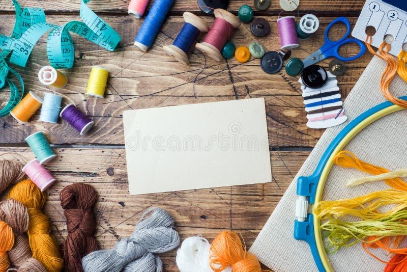 Costurando a ferramenta para o bordado, linhas coloridas centímetro e botões com um par de tesouras na tabela Copie o espaço fotografia de stock