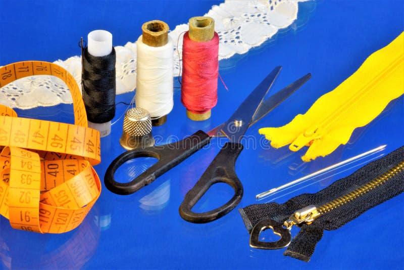 Costurando o alfaiate - um grupo de linhas, tesouras, agulhas, dedal, em um fundo azul criativo, cent?metro para o teste padr?o U fotos de stock royalty free