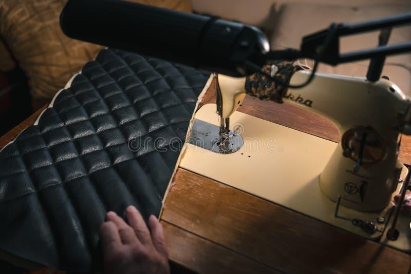 Costurando o processo da correia de couro as mãos do ancião atrás de costurar Oficina de couro costurar do vintage de matéria têx imagens de stock royalty free
