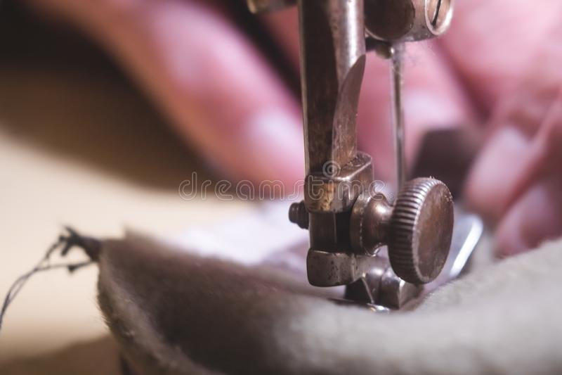 Costurando o processo da correia de couro as mãos do ancião atrás de costurar Oficina de couro costurar do vintage de matéria têx fotografia de stock royalty free