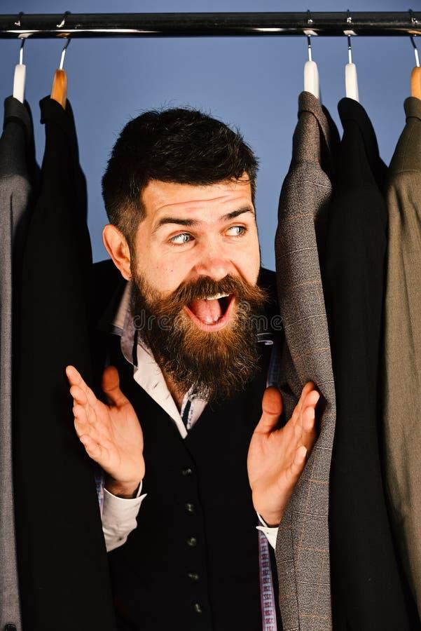 Costure com sorriso curioso perto dos revestimentos feitos sob encomenda no fundo azul fotos de stock royalty free