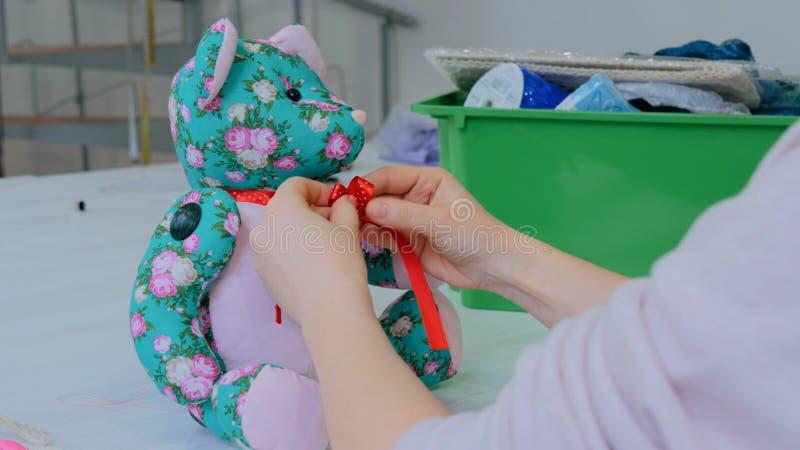 Costure a mulher, toymaker que amarra a curva no pescoço do urso de peluche fotos de stock royalty free