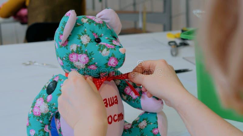 Costure a mulher, toymaker que amarra a curva no pescoço do urso de peluche fotografia de stock royalty free