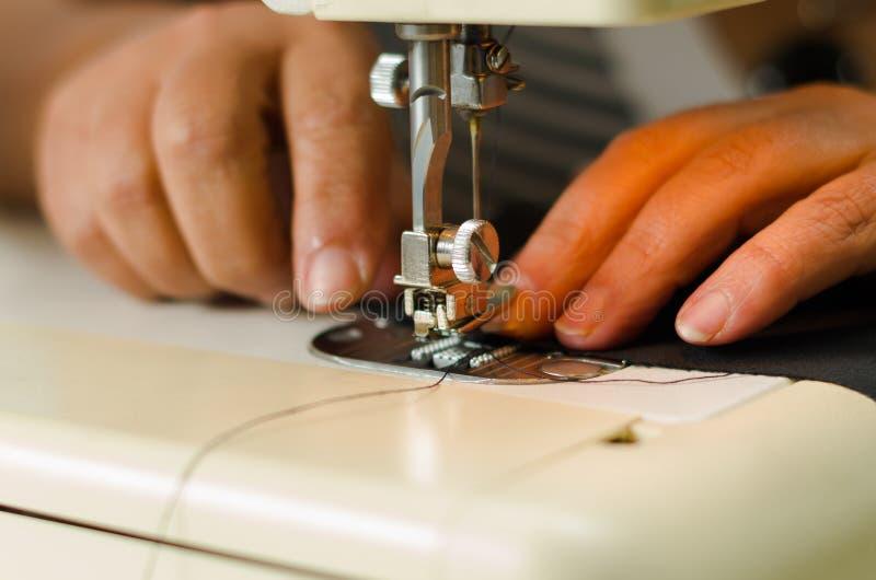 Costure o trabalho em uma máquina de costura, feche-o acima da agulha e rosqueie-o fotos de stock royalty free