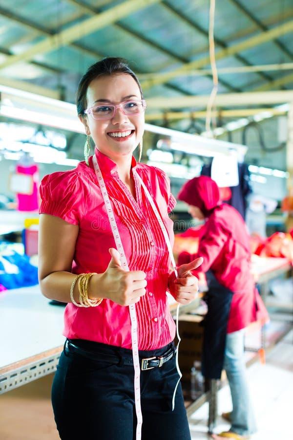 Costureira asiática em uma fábrica de matéria têxtil foto de stock