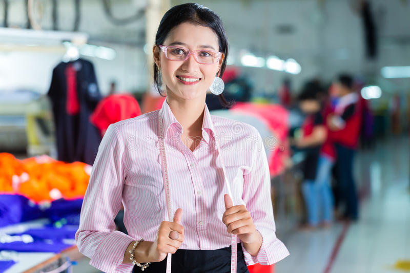 Costureira asiática em uma fábrica de matéria têxtil fotografia de stock