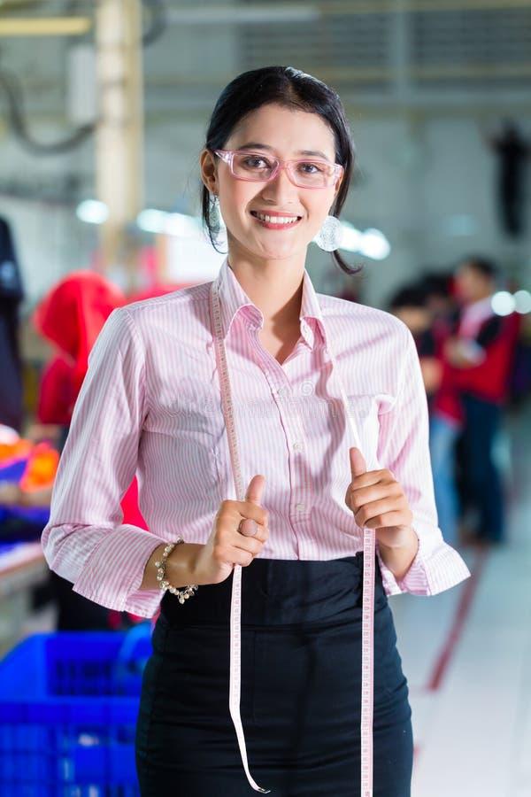 Costureira asiática em uma fábrica de matéria têxtil imagem de stock royalty free