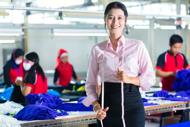 Costureira asiática em uma fábrica de matéria têxtil imagem de stock