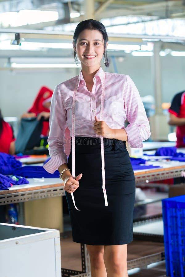 Costureira asiática em uma fábrica de matéria têxtil imagens de stock