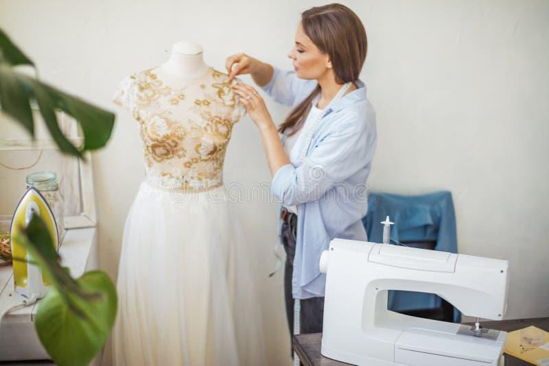 A costureira bonita está trabalhando com um modelo do vestido de casamento em seu estúdio imagem de stock royalty free