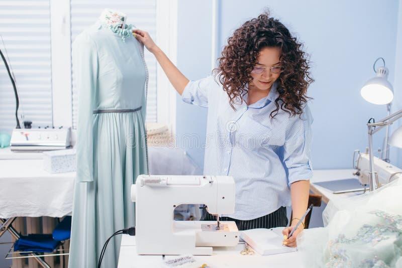 Costureira bonita que escreve medidas do vestido no caderno imagens de stock