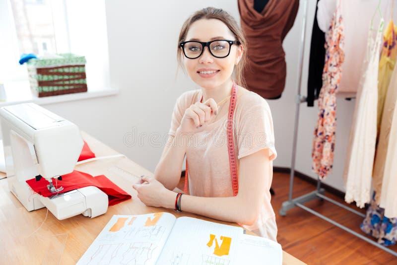 Costureira bonito feliz da jovem mulher que trabalha na máquina de costura fotografia de stock