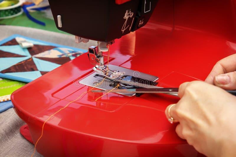 A costureira com tesouras corta a linha na máquina de costura fotografia de stock
