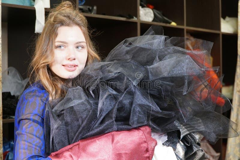 Costureira, costumier ou vendedor guardando um grupo dos vestidos Retrato da mulher no estúdio imagens de stock