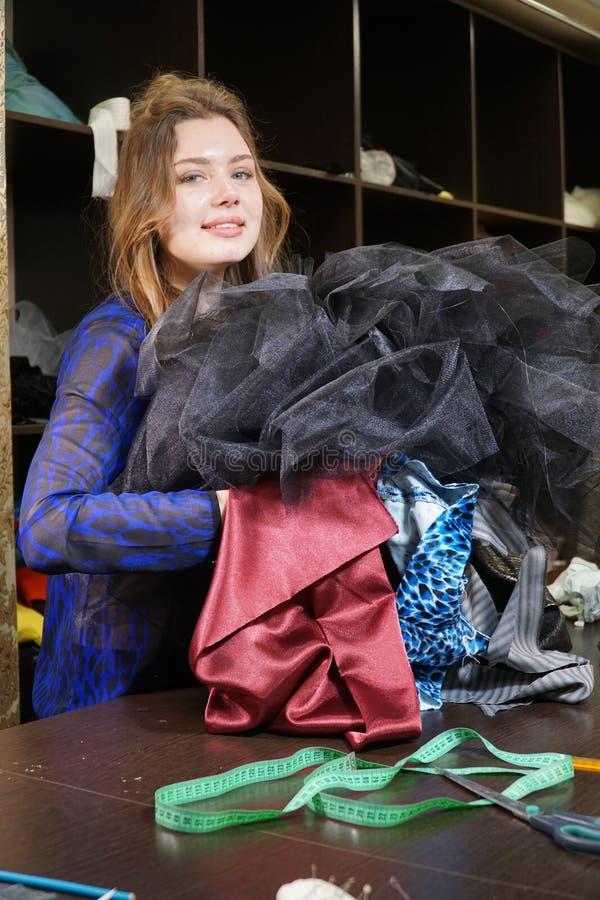 Costureira, costumier ou vendedor guardando um grupo dos vestidos Retrato da mulher no estúdio fotos de stock royalty free
