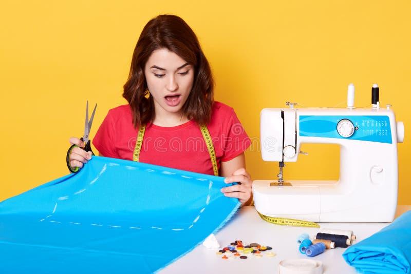 Costureira da jovem mulher que costura em seu estúdio, sendo frustrado porque que faz o erro, se sentando com boca aberta, guarda fotografia de stock