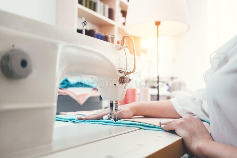 A costureira da jovem mulher que trabalha na máquina de costura costura dentro a sala de exposições Costureira que trabalha com o foto de stock royalty free