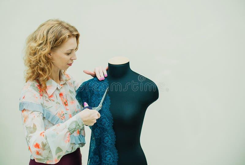 Costureira da mulher que trabalha em seu estúdio O manequim está vestindo um bodysuit do laço O produto é uma cor verde bonita foto de stock royalty free
